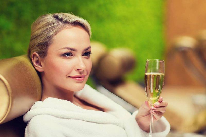 אישה בחלוק שותה יין - גולדן ספא טבריה